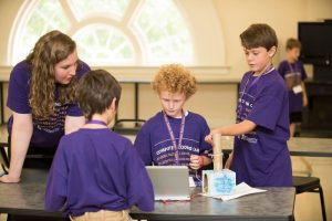an instructor interacts with students at coding camp