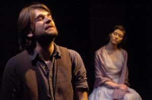 a man sings in the foreground as a woman listens in the background during Molly Sweeney