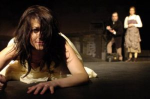 A woman lies in the foreground as foreground as two characters watch in the background in a scene from Macbeth