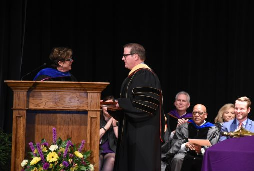 Dr. Jason Newell accepts his award
