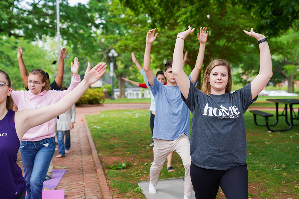 A group of Montevallo students exercise outdoors.