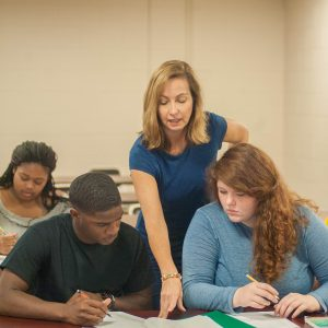 A professor instructs students in the classroom.