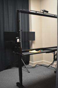 view of the lightboard studio from the doorway showing the monitor displays, camera, and lightboard
