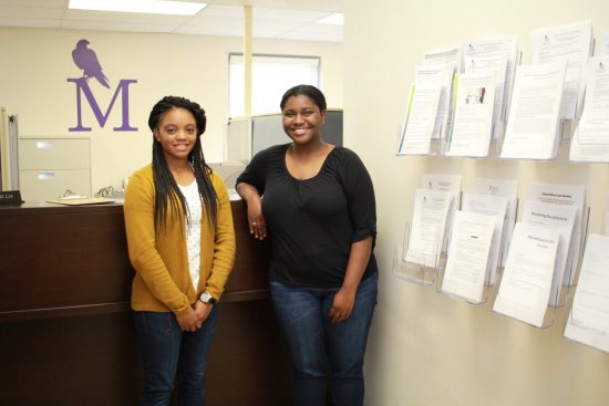Montevallo student employees standing in front of a desk.