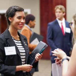 A student speaks with a presenter at a networking fair.