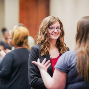 An attendee of a networking fair smiles at a presenter.