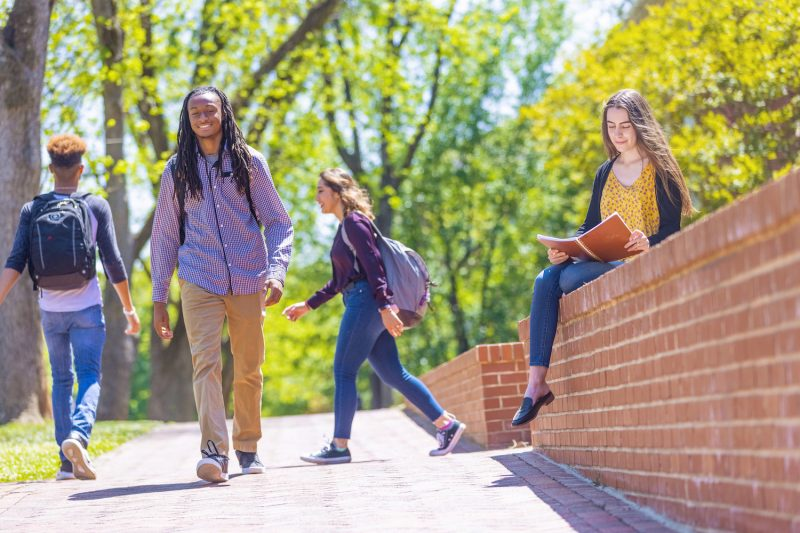 Students walking across campus on a sunny day in the spring.